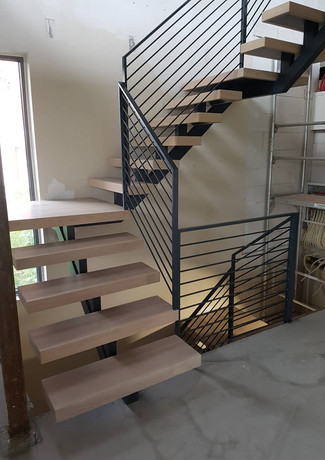 Staircase with thin steel construction and massive steps.