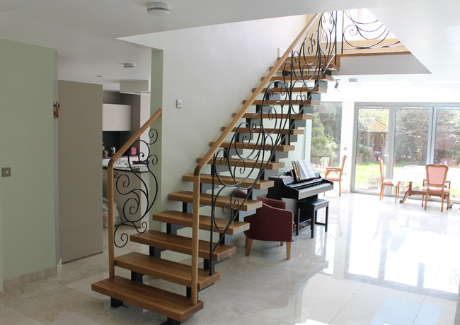 Straight staircase with double steel construction with blacksmith railings.