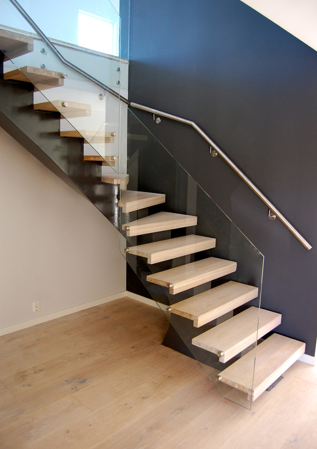 L-shape staircase with black steel construction, white steps from oak and glass railings.
