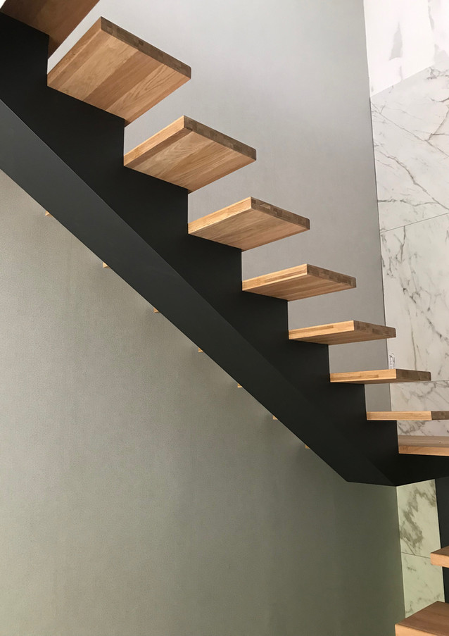 Black painted steel construction staircase with thin steps from oak.