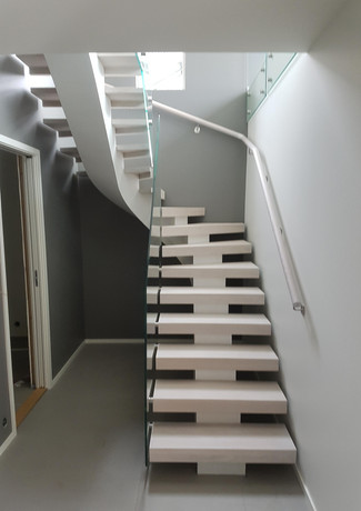 Staircase with white steel construction and white painted oak steps.