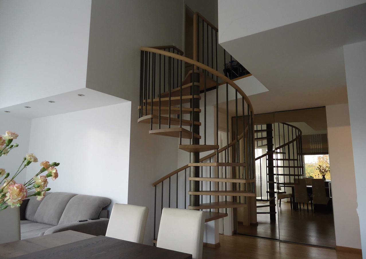 Delicate spiral staircase with a steel beam in the middle, steps from oak and handrails from steel stripes.