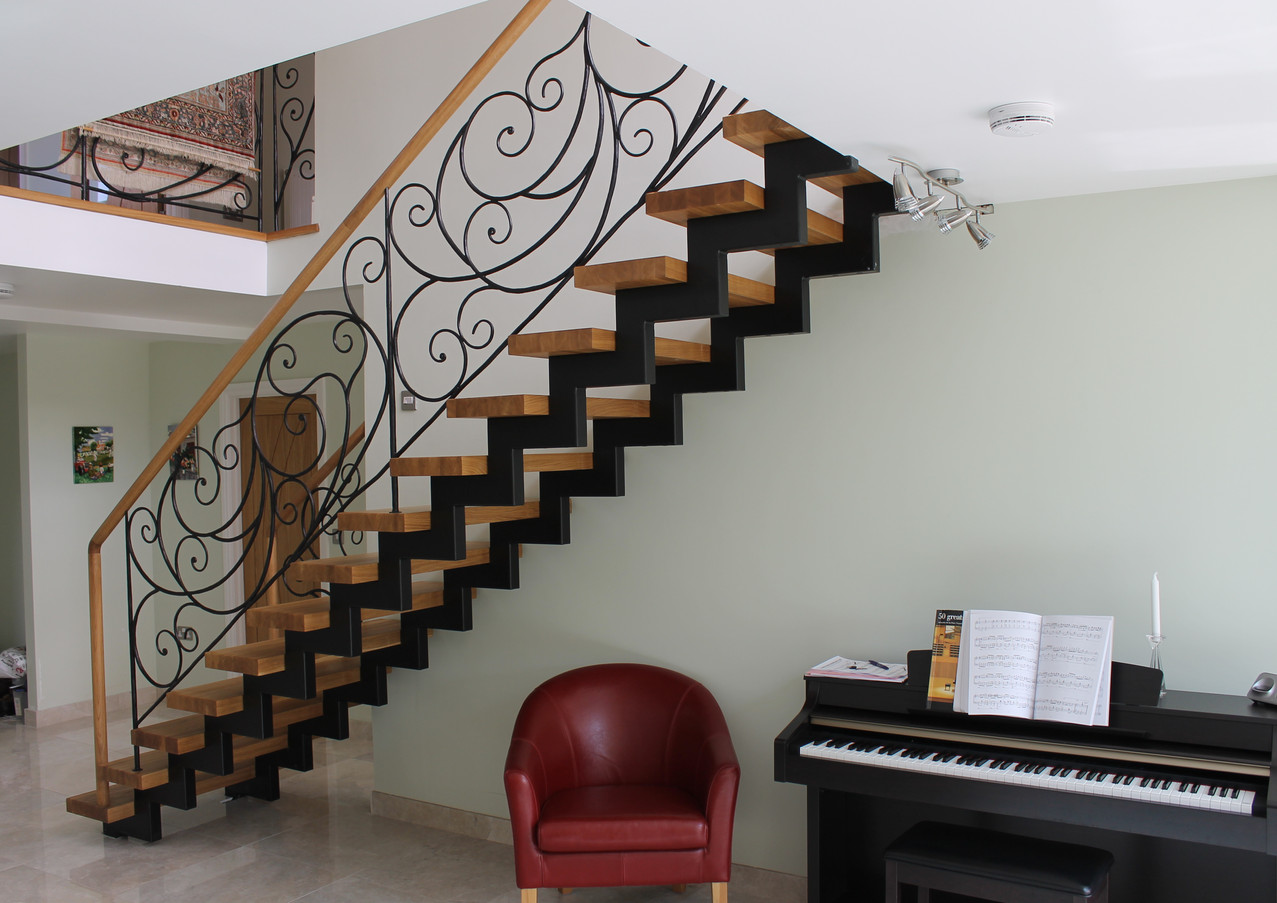 Straight stairs with double steel construction and custom blacksmith railings.
