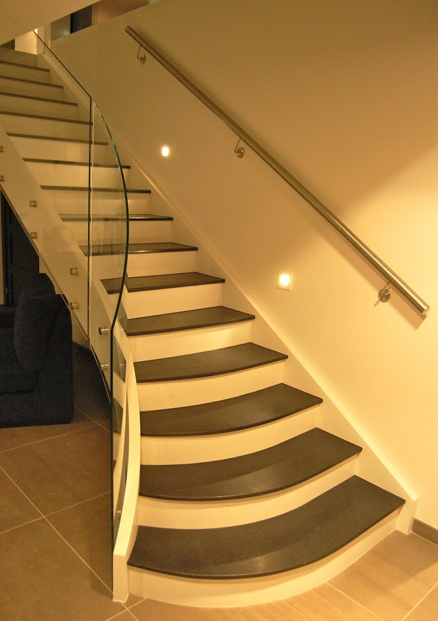 Bright solid construction staircase with glass railings.