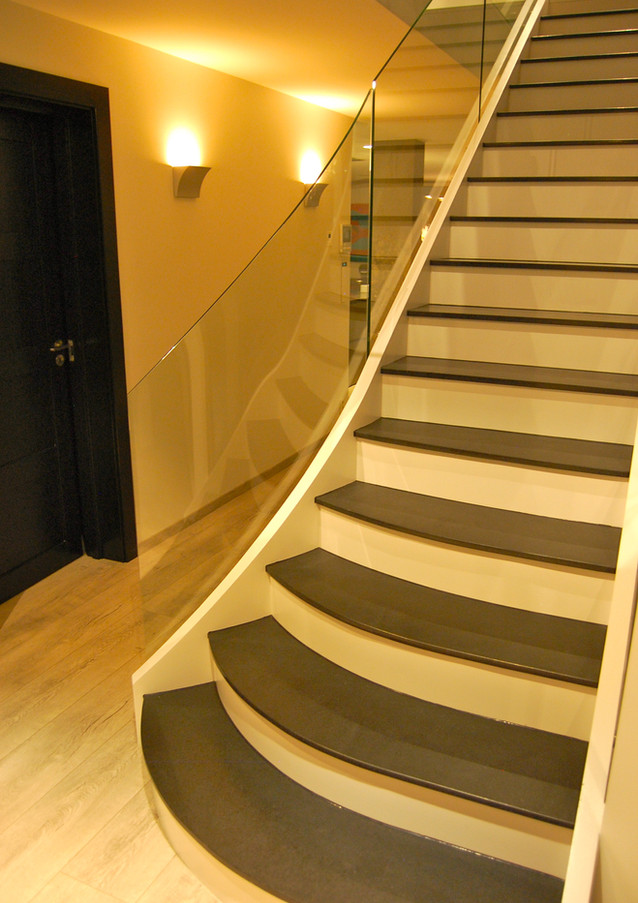 Straight staircase with covered solid steel construction, closed steps and handrail both from curved glass and stainless steel handrail.