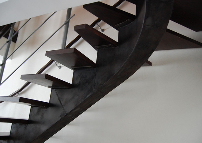 Stairs with black steel construction and dark steps.