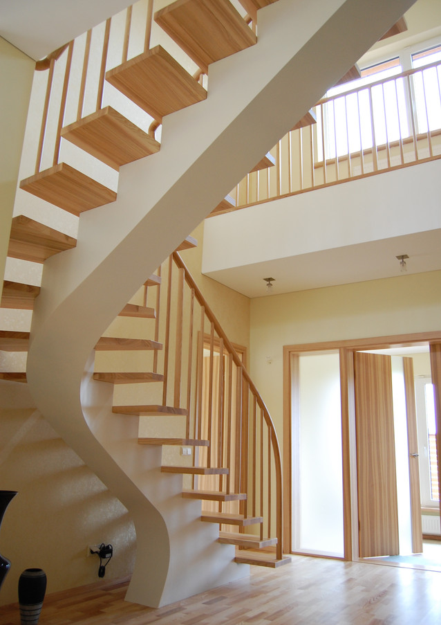 L-shape stairacase with steel construction painted in white and steps from oak with wooden railings.