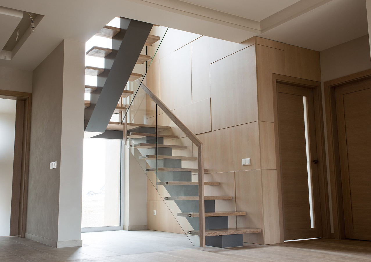 Delicate staircase with steel construction, thin oak steps and railings from glass.