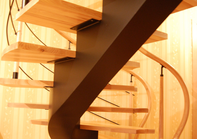 Black steel construction staircase with steps from oak and curved oak handrail.
