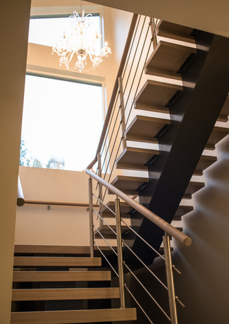 Black painted steel construction stairs with steps from oak and handrails from stainless steel stripes.