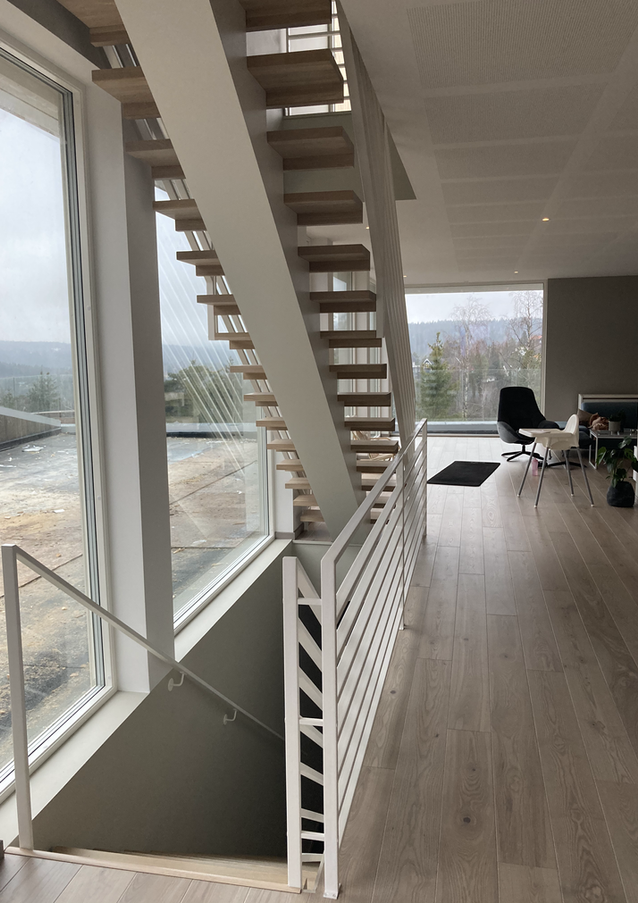 Straight staircase from oak with white-painted steel construction matching the railings.