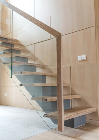 Staircase with grey colour steel construction and railings from glass and wood.
