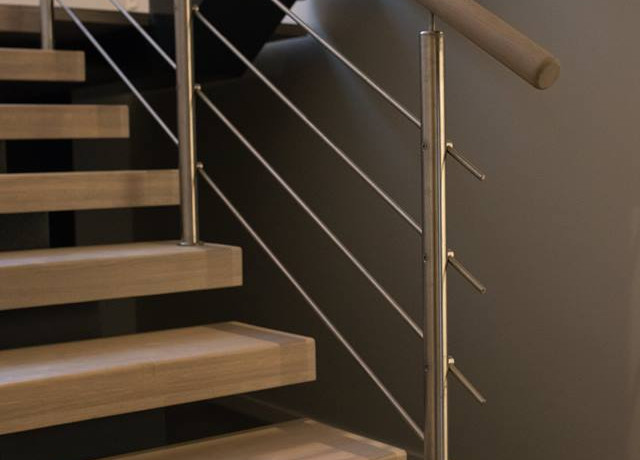 Durable stairs from oak and railings from stainless steel stripes.