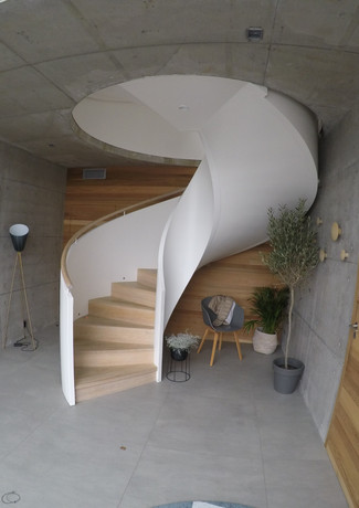 Spiral staircase with covered steel construction and closed oak steps.
