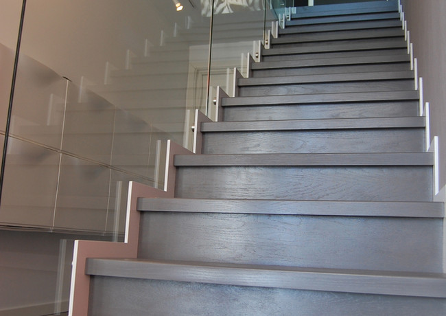 Staircase with steel construction made with laser-cut technology and railings from glass.