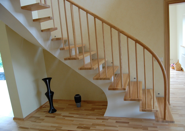 L-shape staircase with white-painted steel construction, steps from oak and railings from oak stripes.