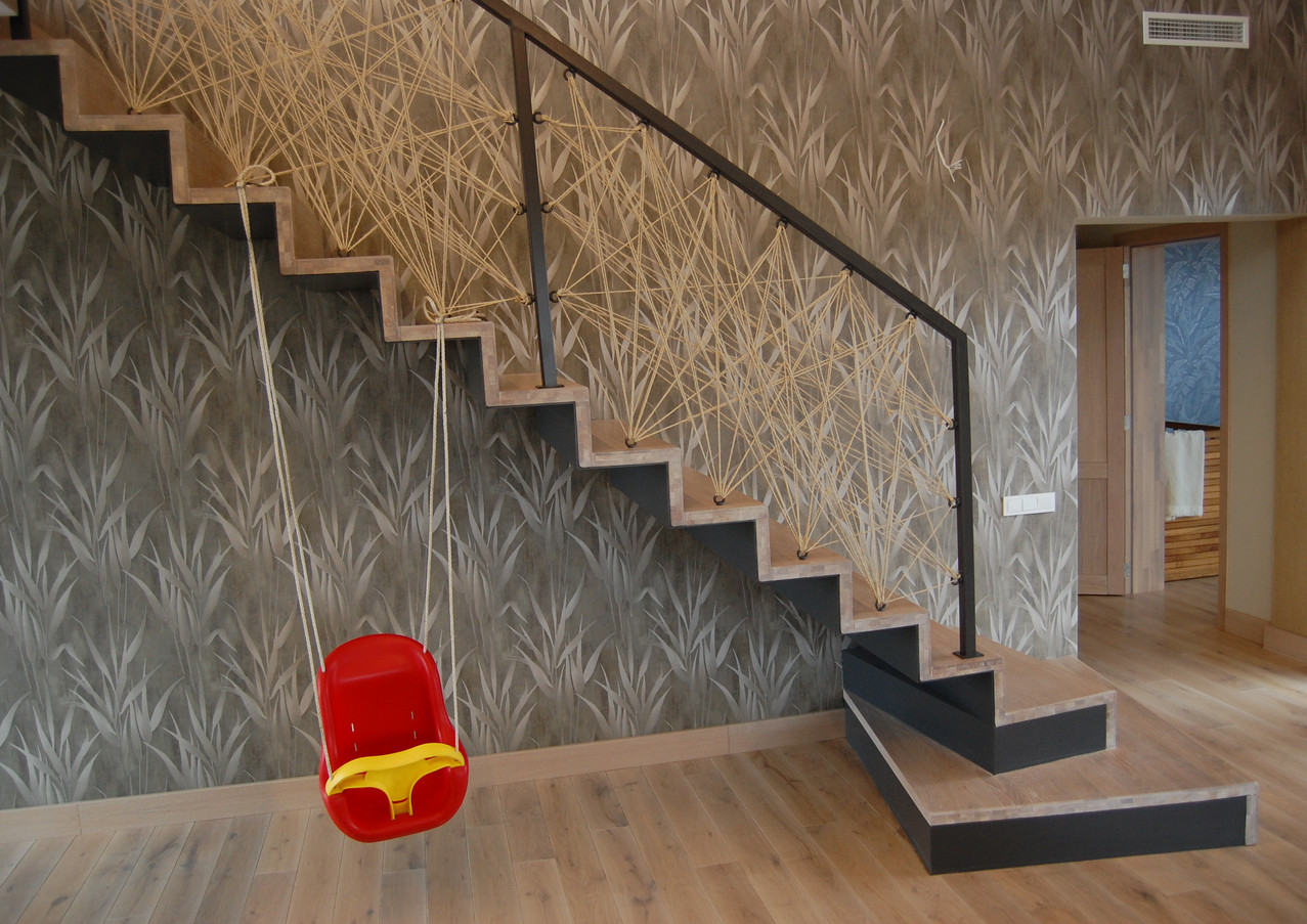 Straight staircase with closed oak steps and custom railings from rope.