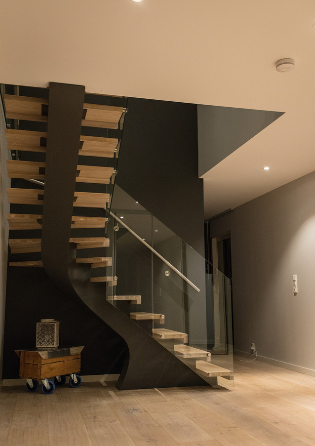 L-shape staircase with darkish steel construction, steps from and railings from glass.