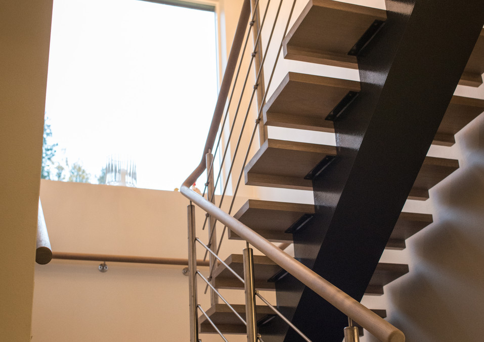 Stairs with steps from oak, railings from stainless steel and dark steel construction.