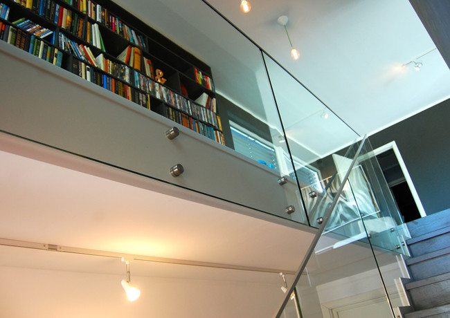 Straight staircase with laser-cut steel construction with closed oak steps painted in grey and railings from glass.