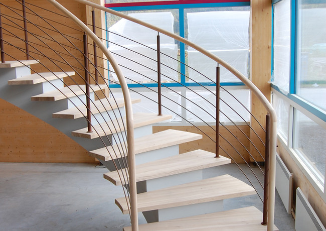 Whitened staircase with white steel construction and oak handrails with metal stripes.