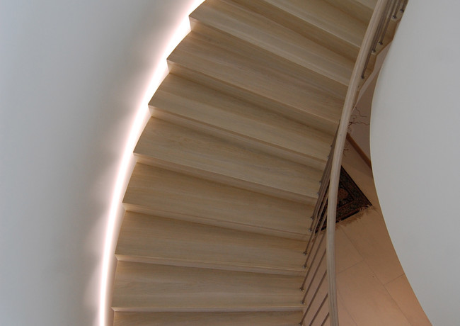 Stairs with solid L-shape steel construction and closed steps from oak, which is also enlightened with LEDs.
