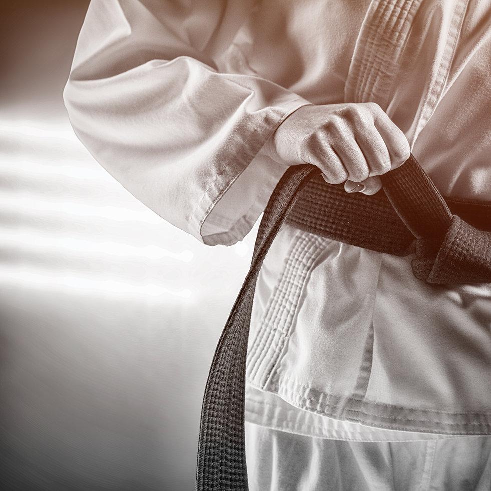 Fighter tightening karate belt against s