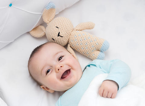 Happy baby newly awake in his crib and w