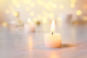 Small candle with light yellow spots on