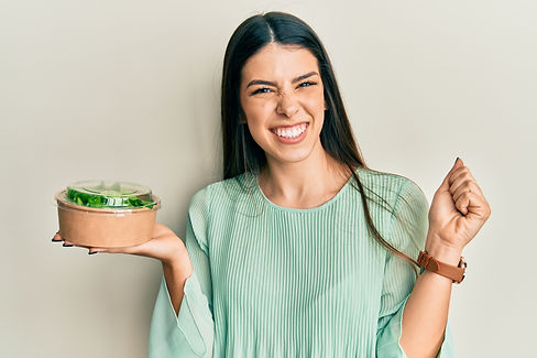 Young hispanic woman eating take away salad screaming proud, celebrating victory and succe