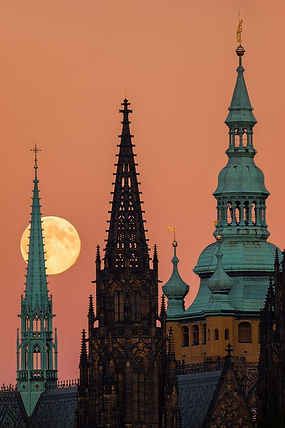 Moonrise behind the towers of St.Vitus cathedral in Prague, Czechia