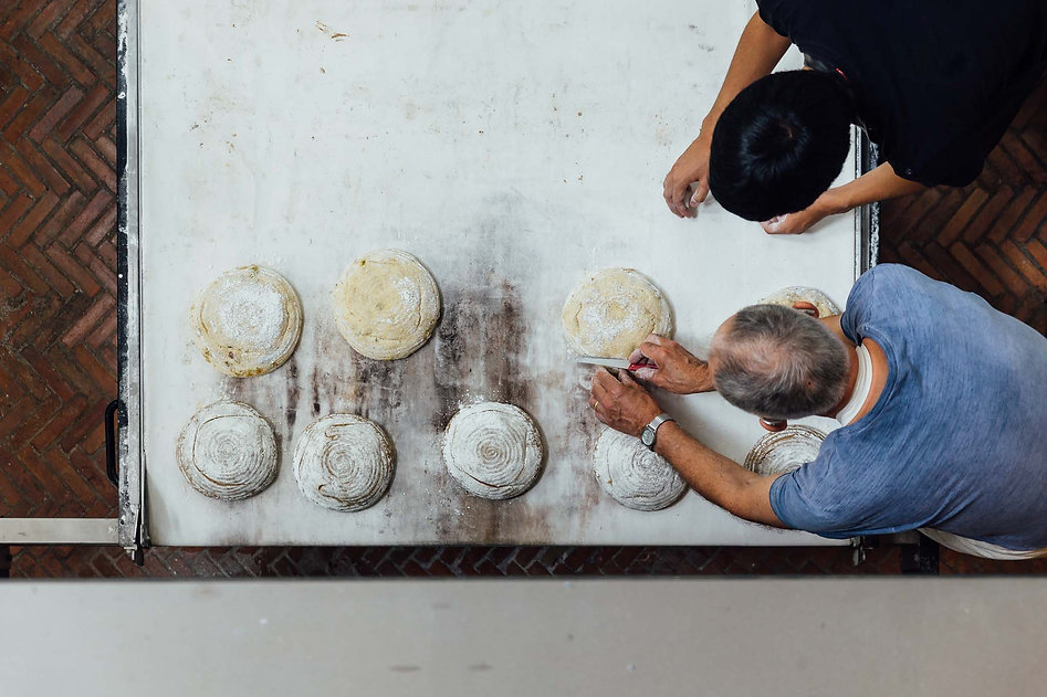 Maurice Chaplais Bakery Consultant cuts Pain Au Levain on oven loader