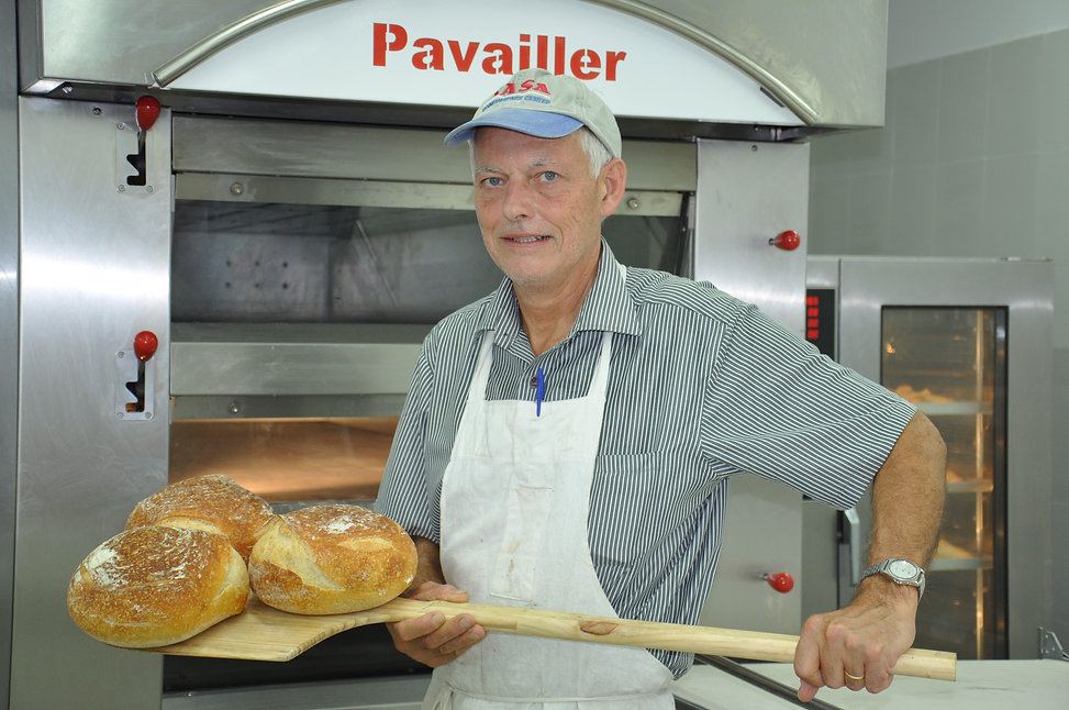 Maurice Chaplais How To Start A Bakery Business Consultant takes sour dough bread from oven in Hyderabad, India