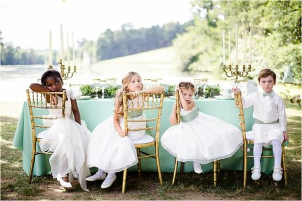 children_sitting_on_chairs_bored_at_wedd