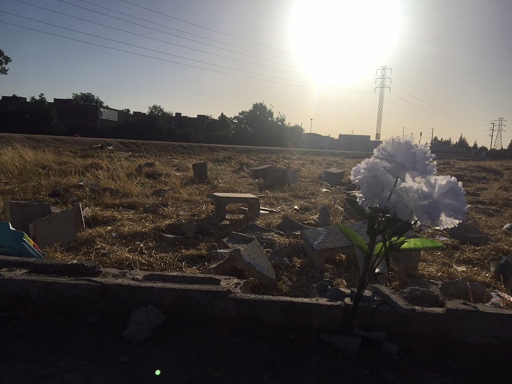 Pieces of the broken wall at the Parks apartment complex and a flower someone left for the deceased