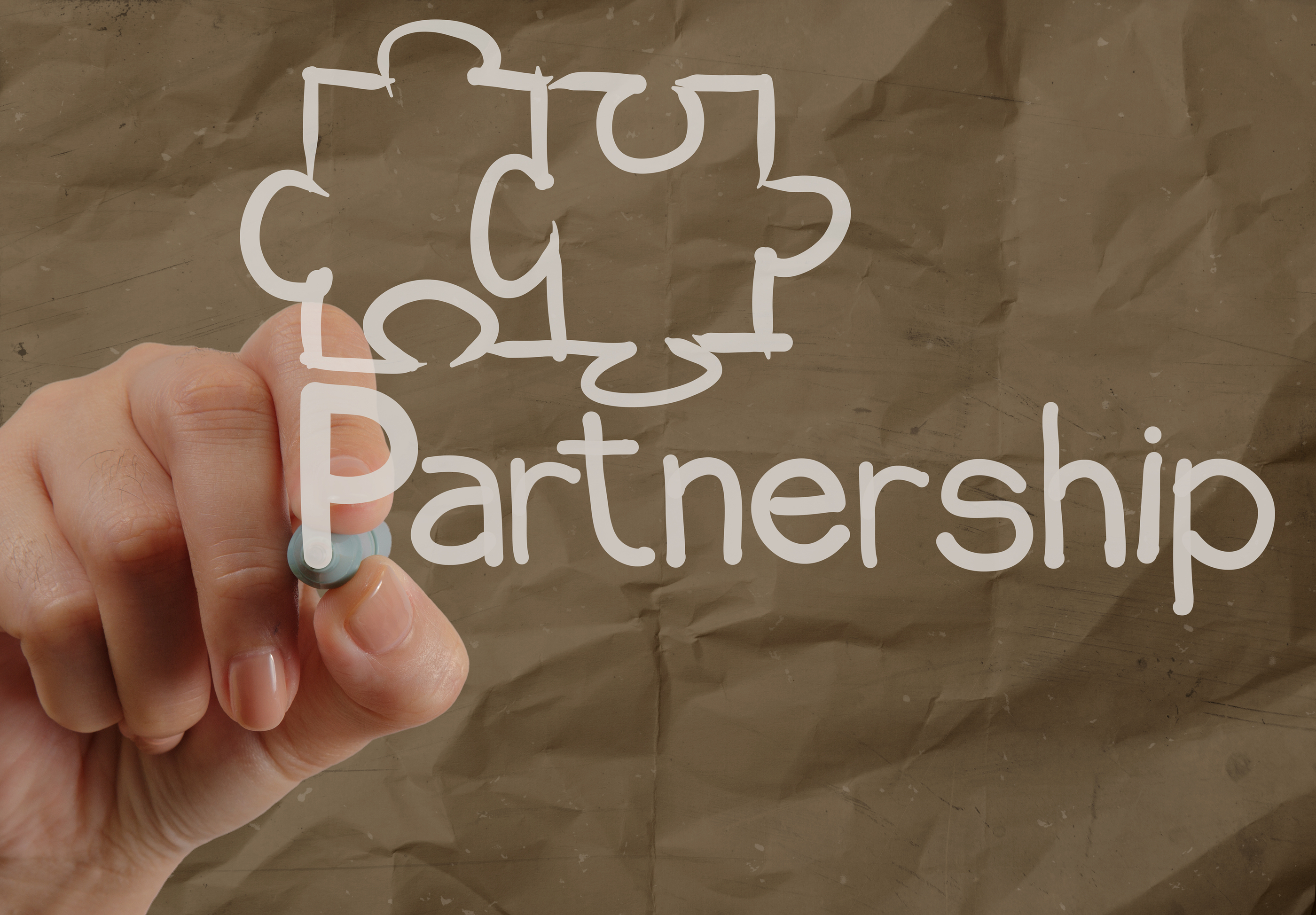 Hand Drawing Partnership Puzzle With Crumpled Recycle Paper Background.jpg