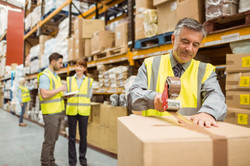 Warehouse worker sealing cardboard boxes for shipping in a large warehouse.jpg