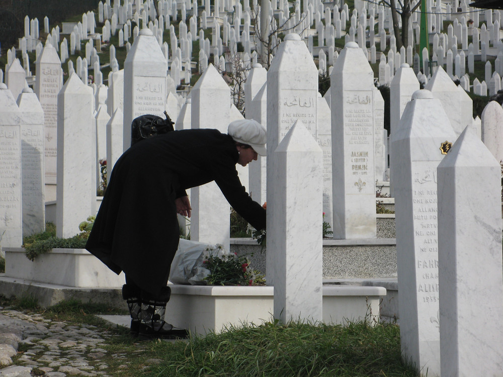 A woman leaves flowers for a loved one lost in the seige of Sarajevo
