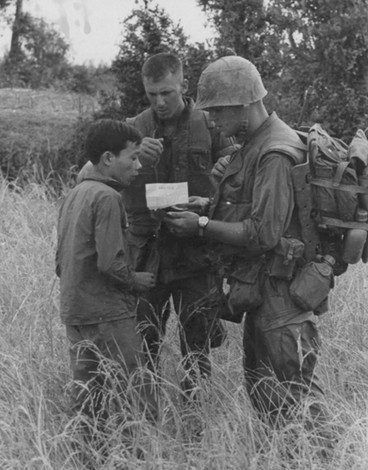 Operation Union--Lieutenant Colonel Esslinger, Commanding Officer of the 3rd Battalion, Fifth Marines, and Corporal O'Neal, S-2 Scout, gives villager 700 piasters for the use of the village as a Command Post.  Source: National Archives photo no. 26387677