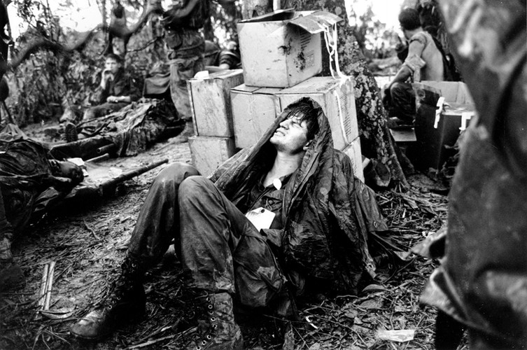 A wounded U.S. paratrooper grimaces in pain as he awaits medical evacuation at base camp in the A Shau Valley near the Laos border in South Vietnam on May 19, 1969 during the Vietnam War.  Source: Hugh Van Es, AP Photo