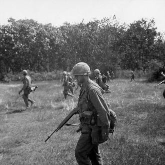 The 1st Infantry Division participates in Operation Crimp. The objective is to seek and destroy a Viet Cong headquarters believed to be in a tunnel complex in or around the Ho Bo woods and close to Saigon. Personnel of the 1st Battalion, 28th Infantry, 1st Infantry Division move through open clearing while conducting their search and destroy mission.   Source: VA029832, Robert Lafoon Collection, The Vietnam Center and Archive, Texas Tech University