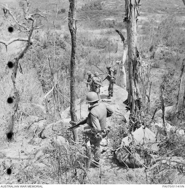 Australian soldiers pause on a rock ledge during their sweep of a section of the Long Hai mountains to survey the ground below during Operation Hammersley. The area was the scene of a bitter battle between a hard-core Viet Cong company and troops of 8th Battalion, The Royal Australian Regiment (8RAR), three days earlier. Bomb scarred trees bear evidence of the pounding the mountains received from land, sea and air strikes.  Wearing flak vests and helmets in the tropical heat took a physical toll on the men. Though D445 Battalion had escaped, the threat of mines remained all too real.   Source: Australian War Memorial item no. FAI/70/0114/VN
