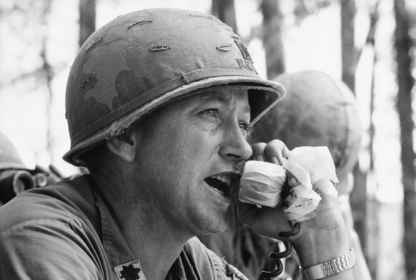 """Lt. Col. Weldon Honeycutt yells orders over field radio to company working its way up a ridgeline toward Dong Ap Bia, the 3,000-foot mountain dubbed """"Hamburger Hill"""" by men of the 101st Airborne, who took it from the North Vietnamese this week, May 23, 1969. Honeycutt commands the Third Battalion of the 187th Infantry's Third Brigade, the unit which overran the well-fortified positions on the hill on the west of the Ashau valley.  Source: Hugh Van Es, AP Photo"""