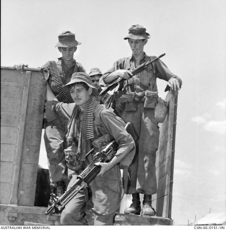 1966-02. Weary and dust-covered after a week of operations in the Ben Cat area north of Bien Hoa, members of 1st Battalion, The Royal Australian Regiment (1RAR), climb down from an Army semi-trailer in the Battalion lines at Bien Hoa. Left to right: Private (Pte) Rick Jeffrey of Traralgon, Vic; Pte Graham Lobb (with M60 machine gun) of Reservoir, Vic; Pte Lindsay Dalton of Riverstone, NSW. The soldiers had been taking part in Operation Rolling Stone with elements of the US 1st Infantry Division.  Source: Australian War Memorial item no. CUN/66/0151/VN