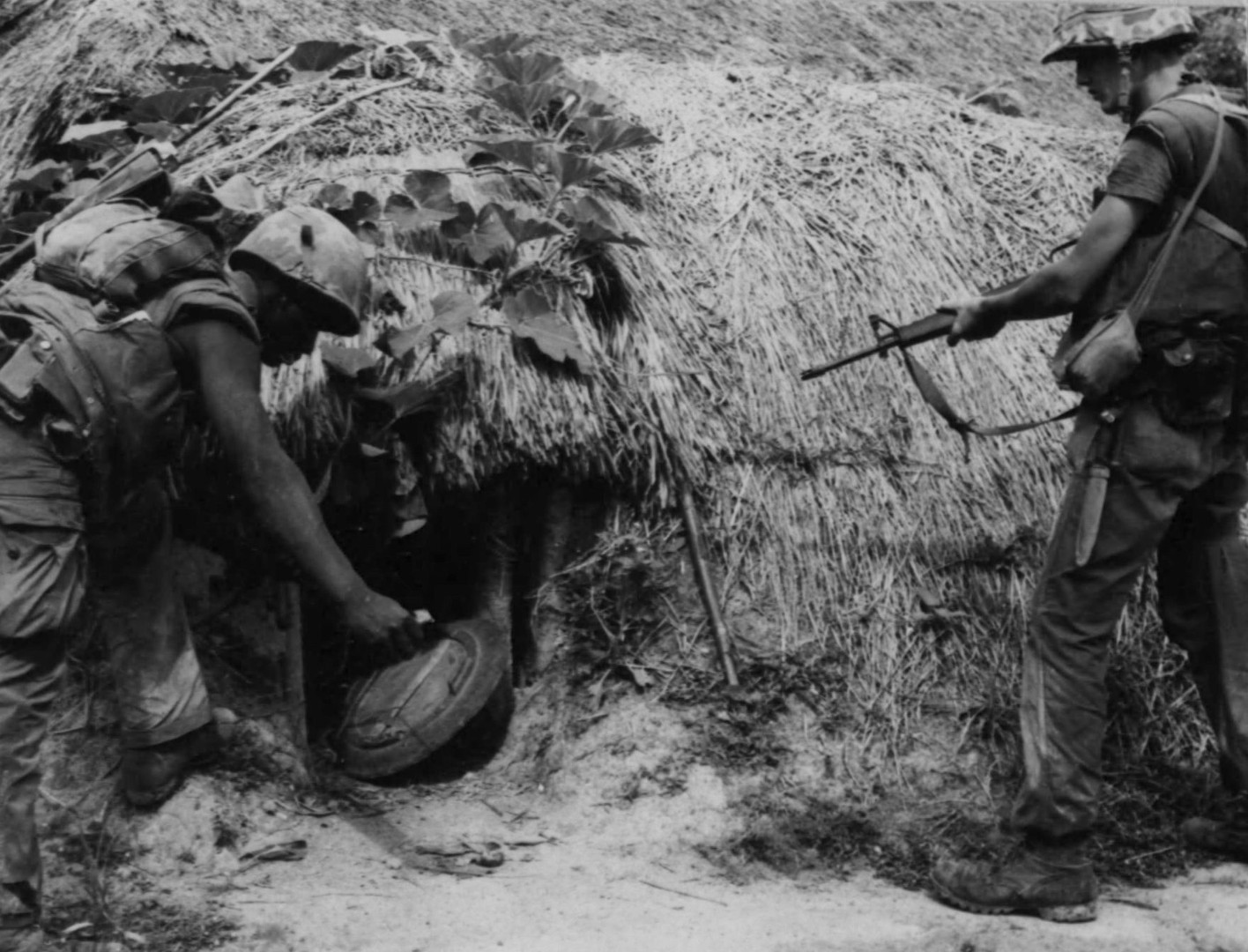 Operation Union--Private First Class [illegible] J. Hill (Schenectady, N.Y.)  of Hotel Company, 2nd Battalion, First Marines, tosses a grenade through an entrance of a Viet Cong hut while Private First Class Angelo D. [illegible] (Rocky Hill, Conn.) prepares for any Viet Cong resistance.  Source: National Archives photo no. 26387681