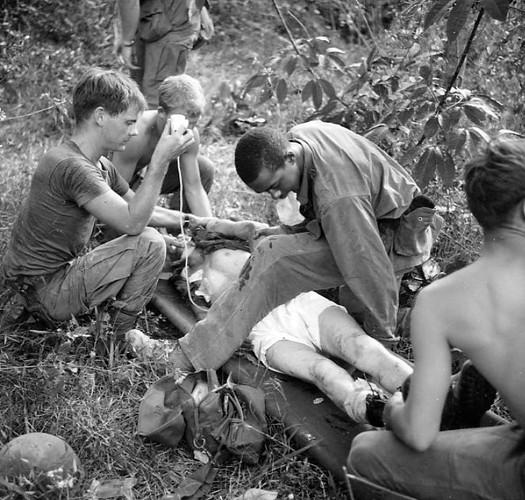 The mission of C Company, 1st Battalion, 5th Mechanized Infantry, 2nd Brigade, 25th Infantry Division was to sweep through the Filhol Plantation in search of fleeing Viet Cong units. During a sweep, some Viet Cong were spotted and fled. Soldiers of the company dismounted their M113 Armored Personnel Carriers and pursued. During the pursuit, a soldier tripped a booby trap. Three men were wounded, one seriously. SP4 Ronald P. Jenkins, medic, attended the wounded and then the three were evacuated. SP4 Jenkins lifts the legs of a wounded soldier to check for additional wounds. Another soldier assists by holding an IV, while two stand by to lift and carry the stretcher.   Source: VA029741, Robert Lafoon Collection, The Vietnam Center and Sam Johnson Vietnam Archive, Texas Tech University