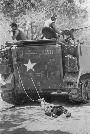 24 February, 1966  The body of a Viet Cong soldier is dragged behind an American armored vehicle en route to a burial site after the Battle of Suoi Bong Trang during the Vietnam War.  Source: Kyoichi Sawada, United Press International