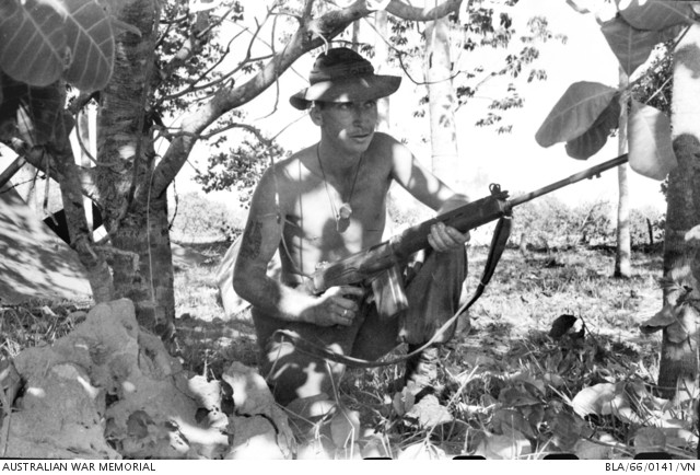 1966-02-20. Wide-awake look from Private (Pte) Jock Richards of Scarborough, Perth, WA, as he guards an Australian encampment during Operation Rolling Stone in Viet Cong country near Ben Cat, South Vietnam. Pte Richards is serving with the 1st Battalion, The Royal Australian Regiment (1RAR), based at Bien Hoa.  Source: Australian War Memorial item no. BLA/66/0141/VN