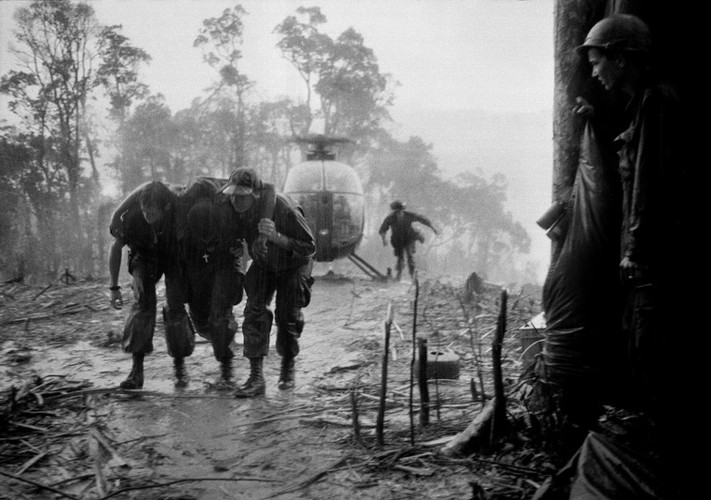 A wounded U.S. paratrooper of the 101st Airborne Division is helped through a blinding rainstorm by two medics after being evacuated from Dong Ap Bia during the 10-day battle for Hamburger Hill, May 1969. U.S. and South Vietnamese forces eventually dislodged communist forces from Dong Ap Bia, but the action touched off further political controversy in the United States.   Source: Hugh Van Es, AP Photo