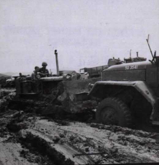 A D-8 tractor from the 173rd Engr Co, attached to the 173rd Abn Bde, pulls a 5-ton ammunition truck out of the mud during Operation Greely. 16 July 1967.